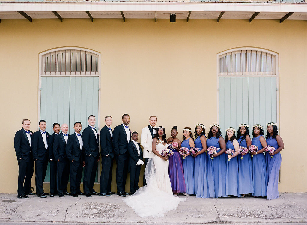 bridesmaids in purple dresses with groomsmen standing in a line in front of a yellow wall with green shutters