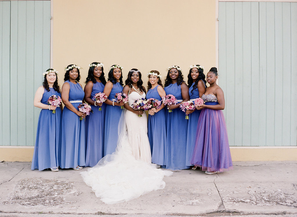bride with bridesmaids standing together in a row, in purple ombre dresses holding flower