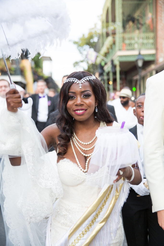 Nigerian bride holding second line parasol umbrella walking in the street after her wedding ceremony