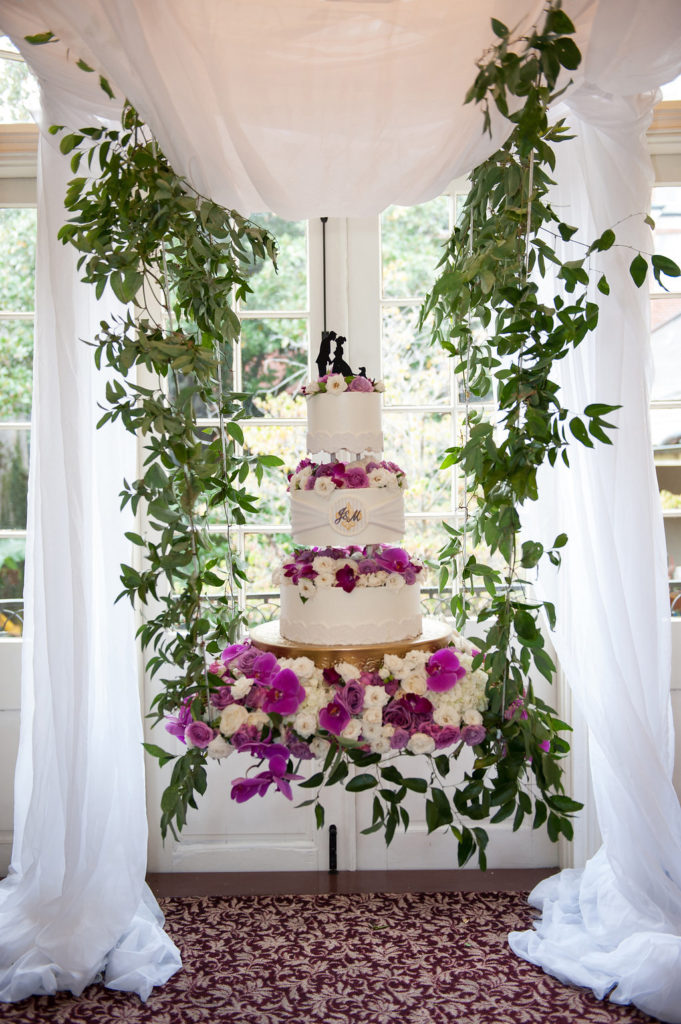 white cake with purple flowers suspended by greenery vines under a white drape structure inside a wedding venue