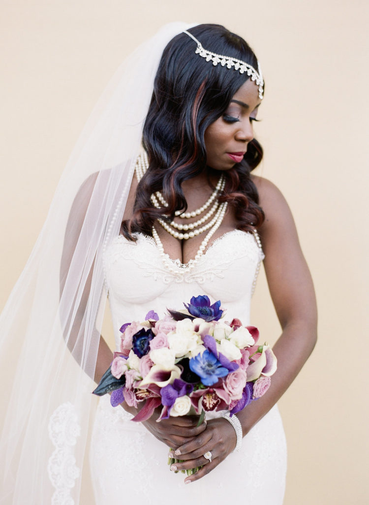 bride wearing jewel frown, white dress, multi strand pearl necklace with purple and white floral bouquet looking down