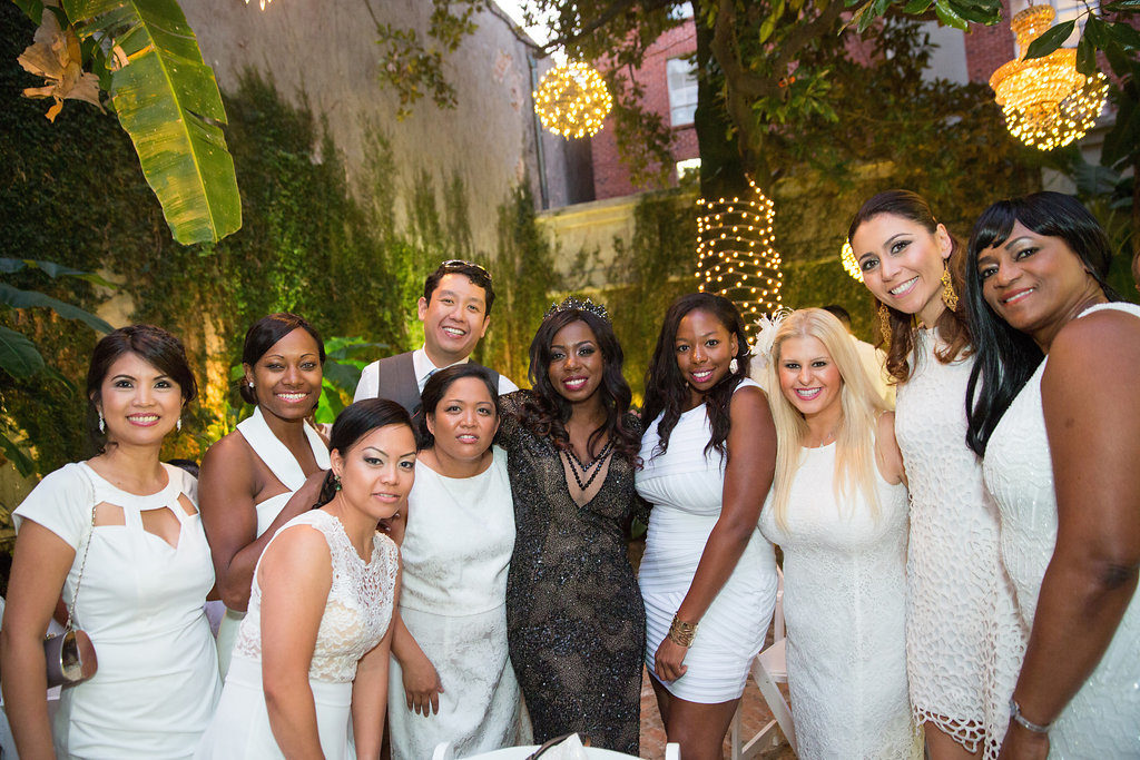 bride standing with guests dressed in all white in a private courtyard wedding reception