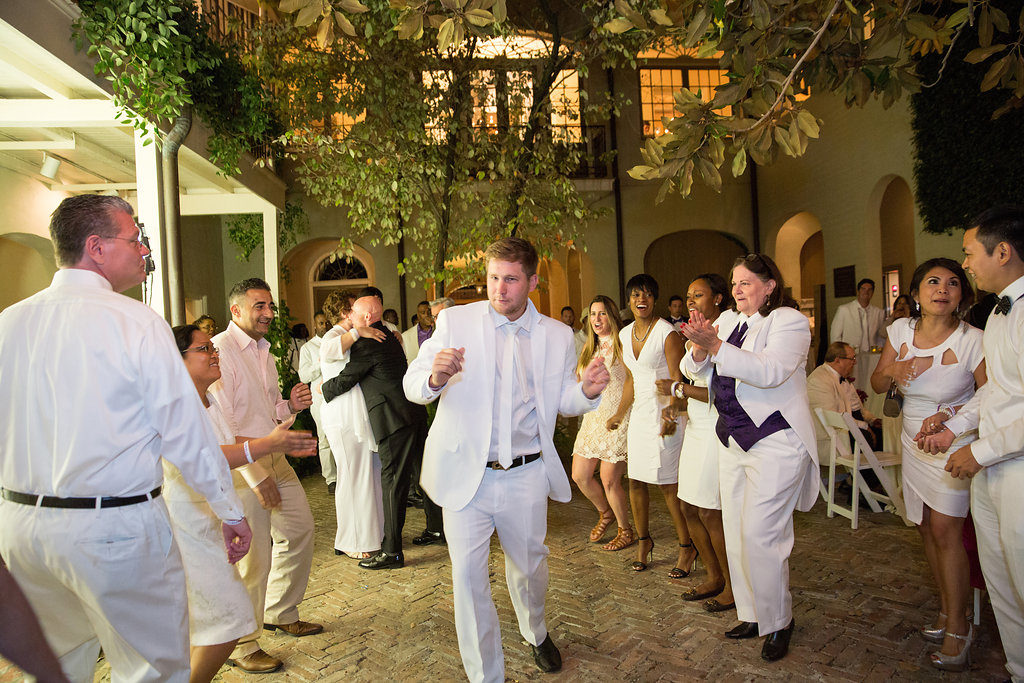wedding guests dressed in all white dancing in a courtyard wedding reception