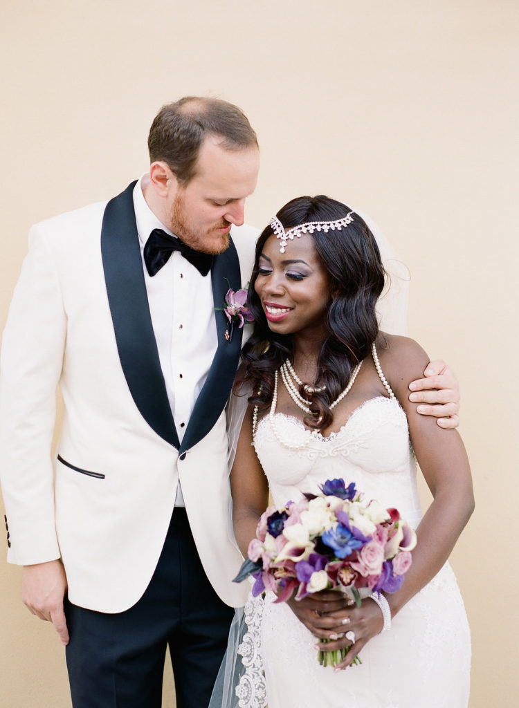 Nigerian bride and white groom in black tie wedding attire with bouquet holding each other