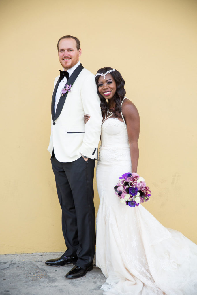 newlyweds standing next to each other smiling at the camera, while bride holds her purple and white bouquet at her side and grasps his left arm