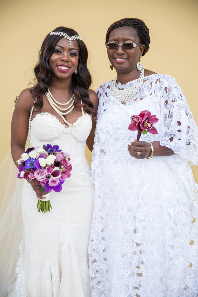 Nigerian bride and her mother both dressed in white, holding purple floral boquuets