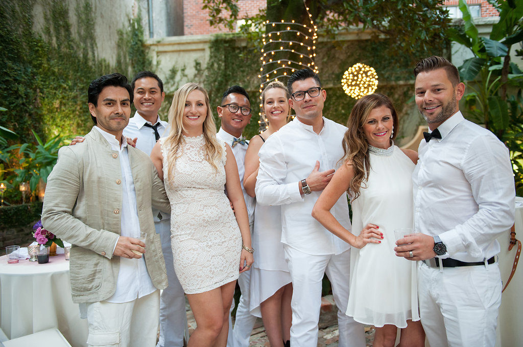 wedding guests in a group dressed in all white outdoors in a courtyard smiling at the camera