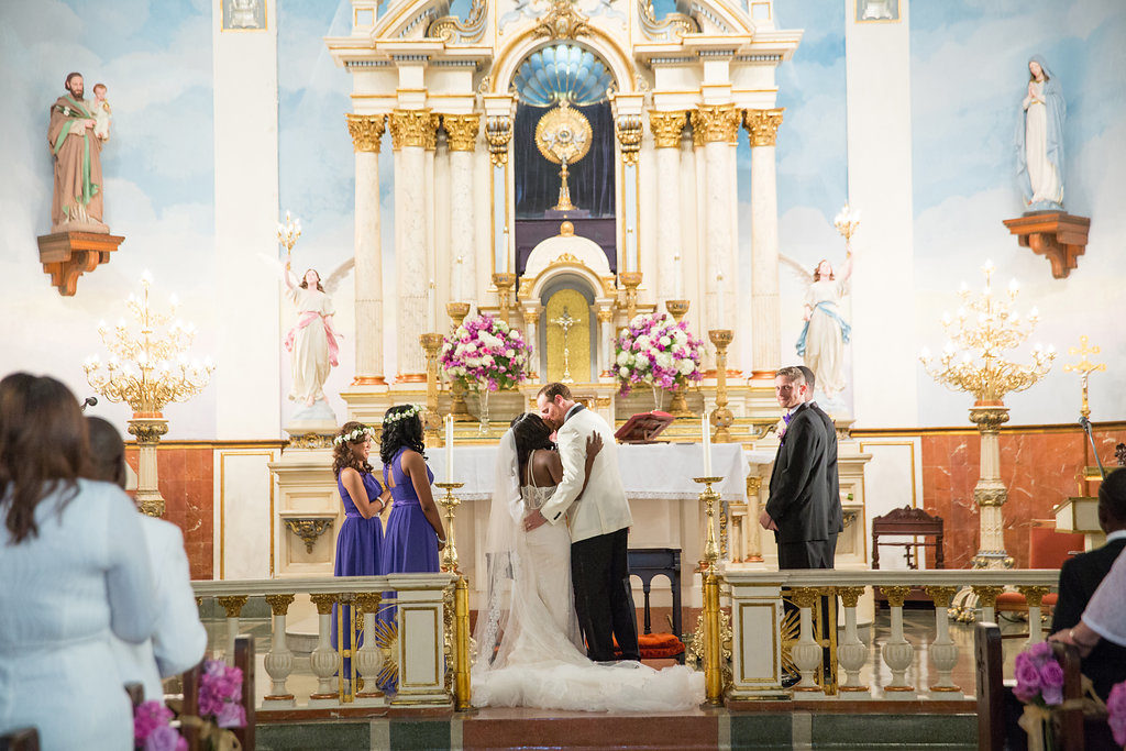 intimate wedding ceremony at St. Mary's Italian Church in New Orleans as bride and groom kiss
