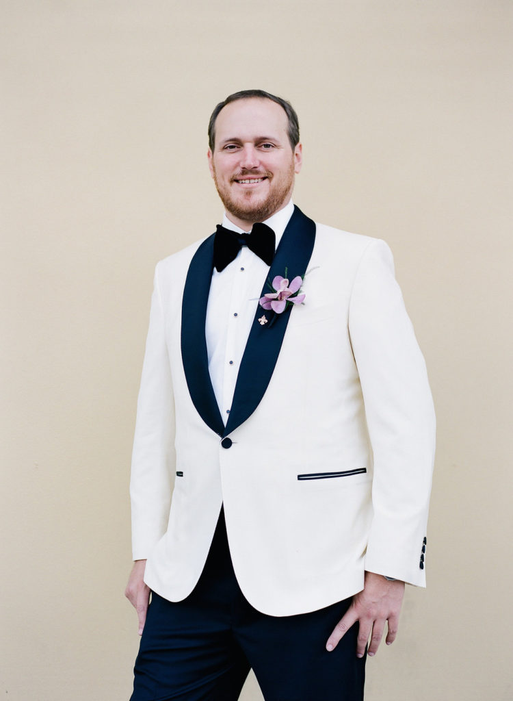 groom in white tuxedo jacket with black lapel, black tuxedo pants, and purple boutonniere