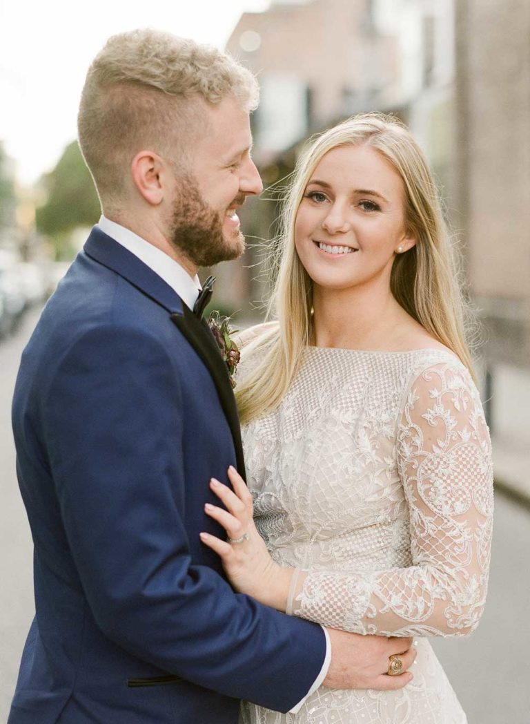 newlywed portrait smiling outside wedding venue