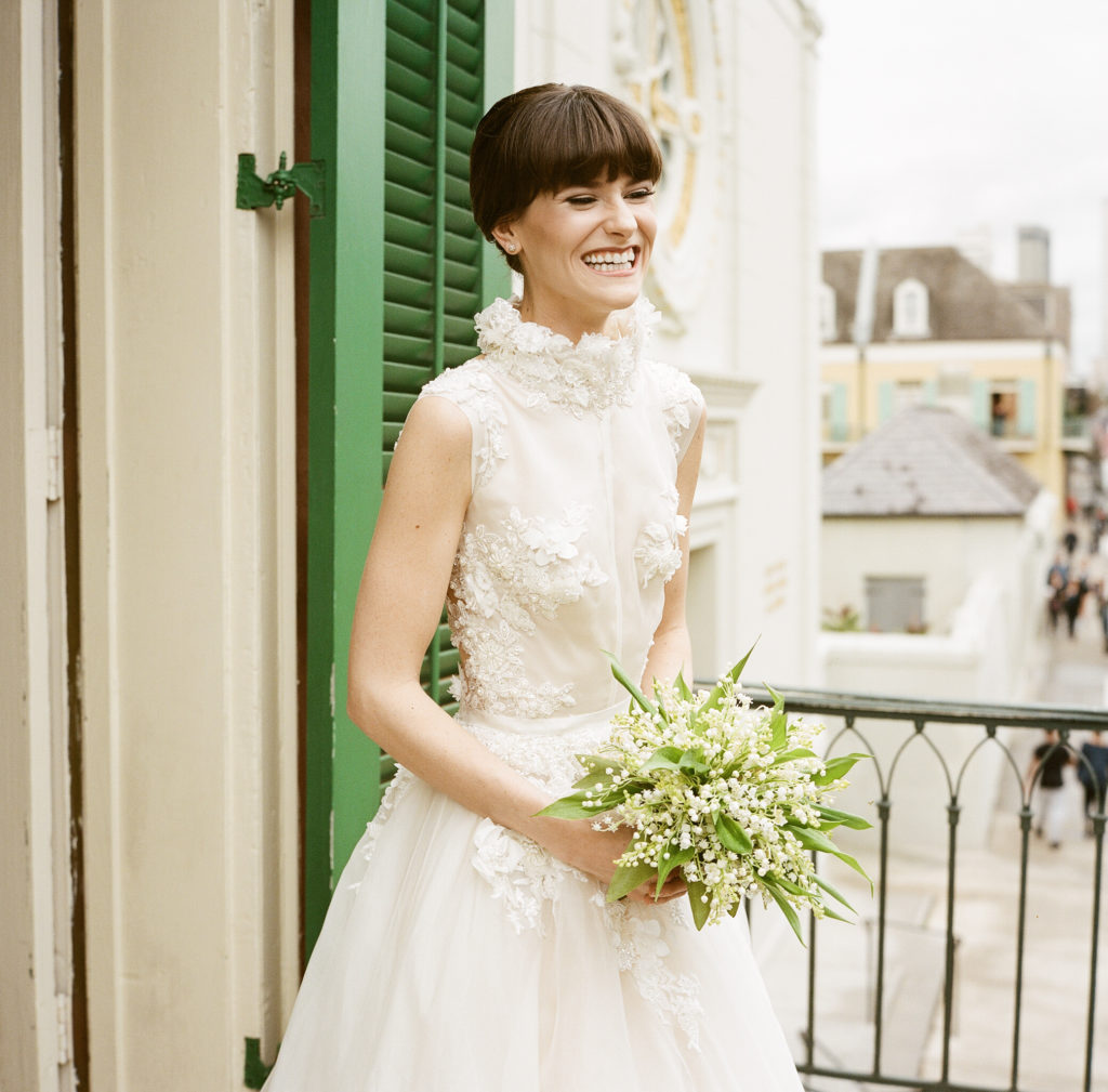 bride smiling and holding a bouquet of lily of the valley flowers