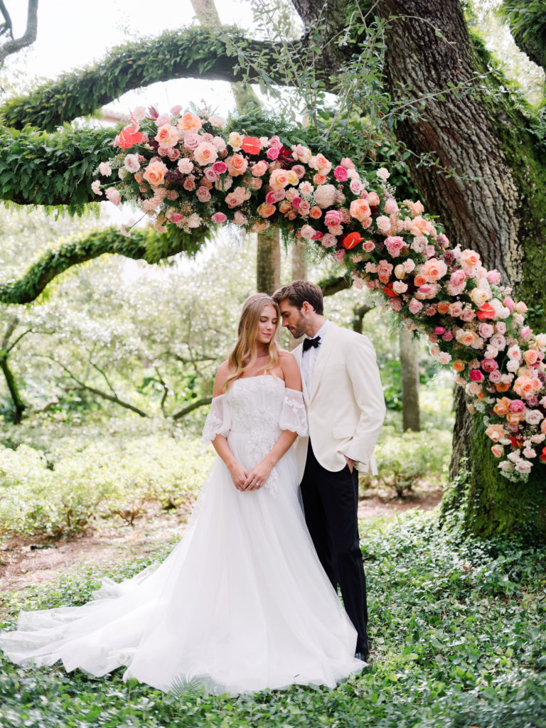 pink red and peach flowers climbing a tree behind a bride and groom at Sea Island, Georgia