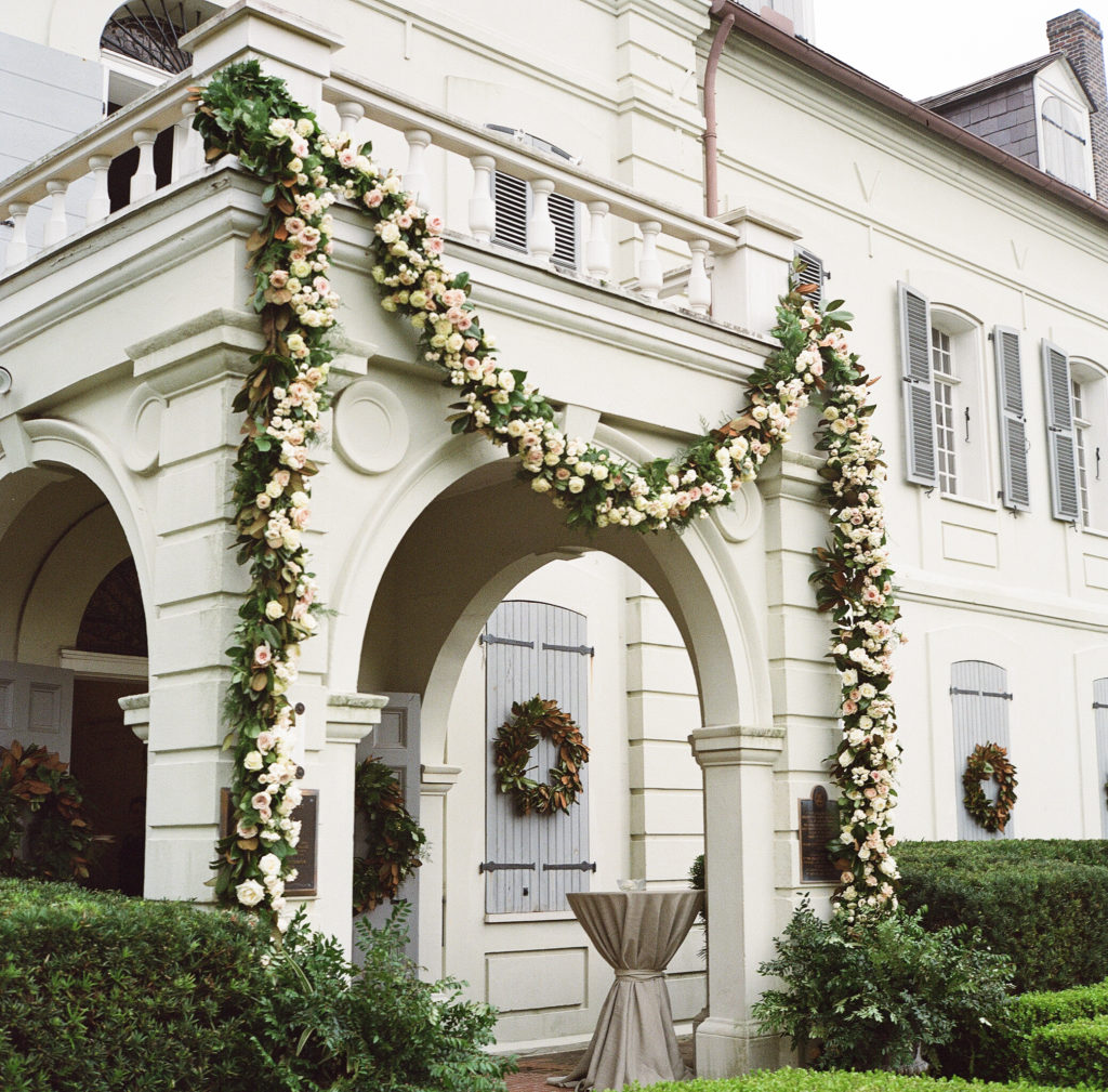 garland of white and blush flowers and greenery draped across the portico entrance of a building