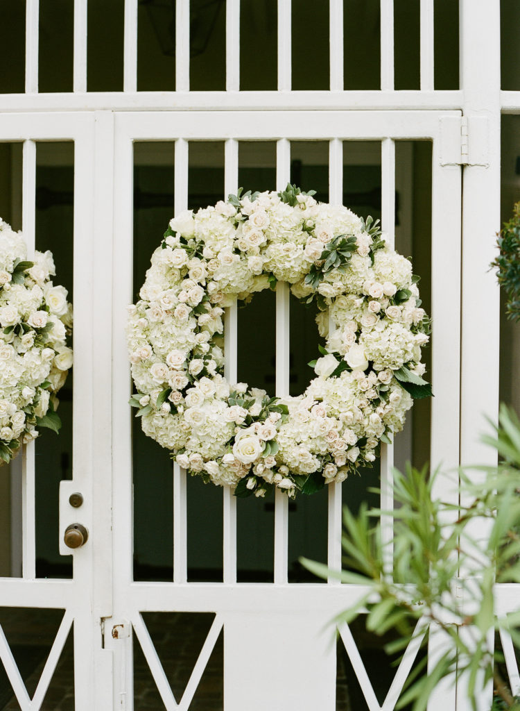white and green floral wreaths on the front of a white gate