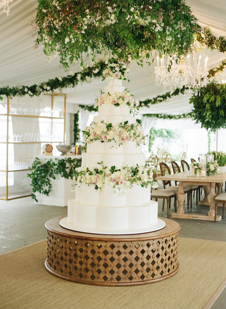 large white cake with pink and white flowers and green leave between the layers, in a tent with green garlands everywhere
