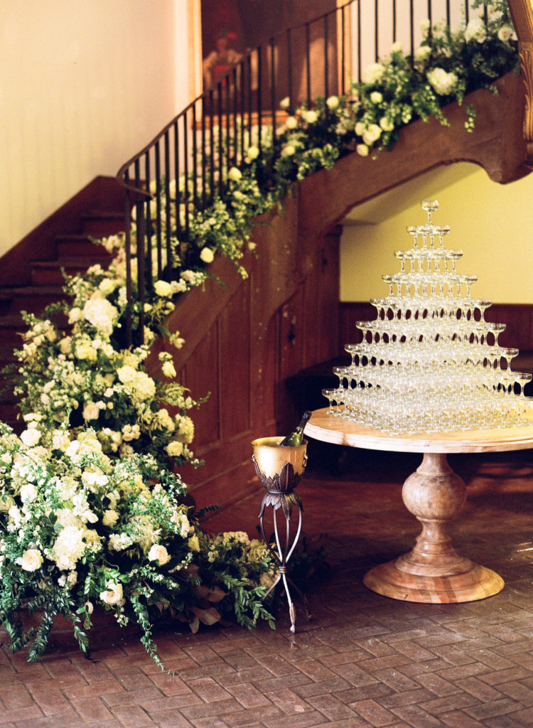 white and green flowers climbing down a staircase with a table of champagne glasses stacked in a pyramid