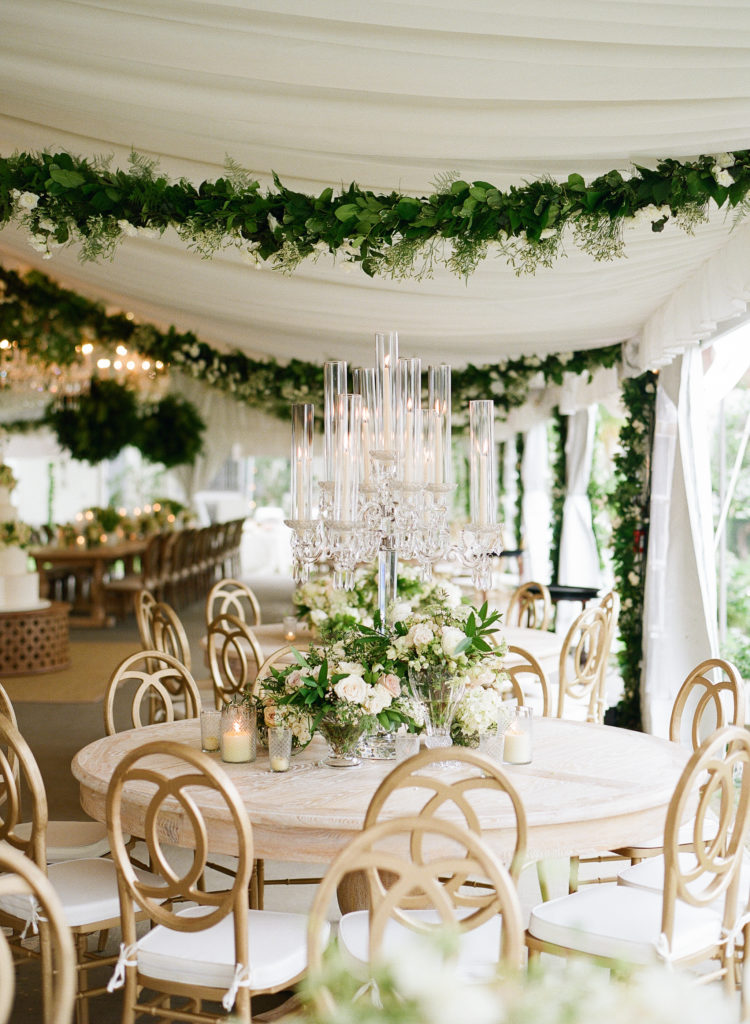 dinner table with white and green flowers and tall clear crystal candelabras in a tent with green garlands