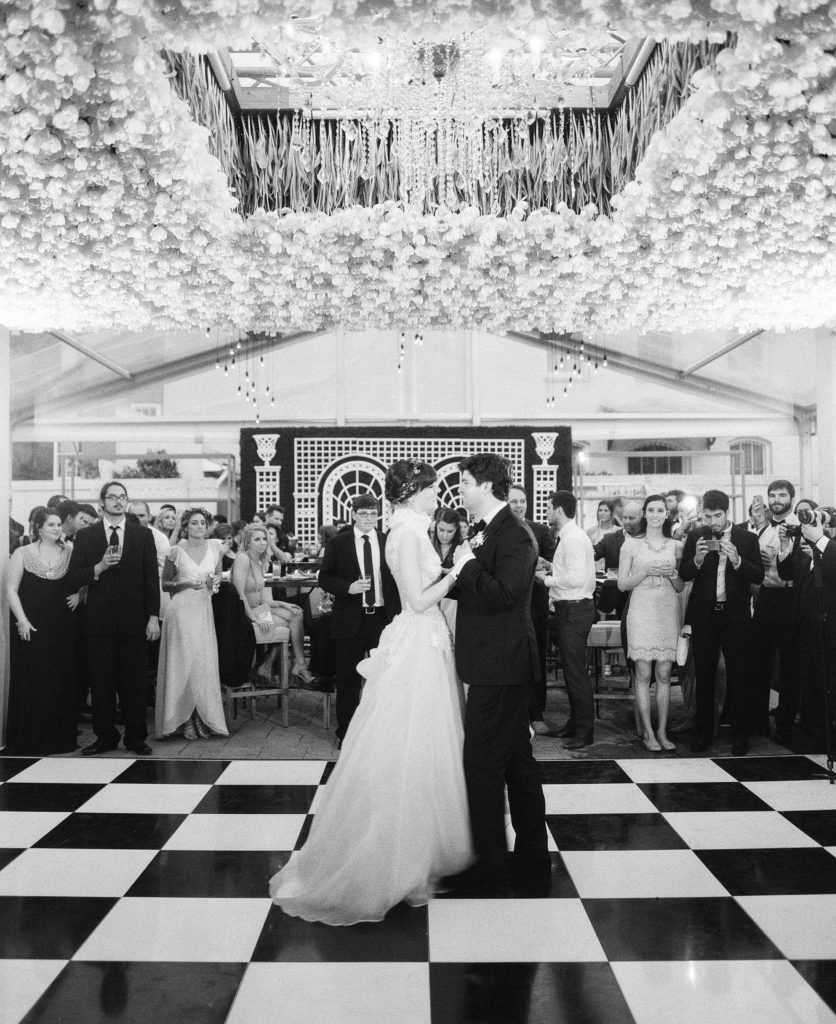 bride and groom dancing  under a floral ceiling with a black and white dance floor