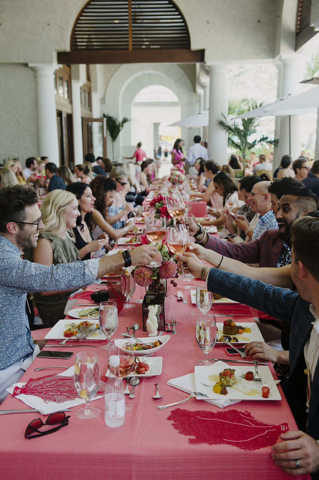 picture of people eating and drinking lunch at a long table in a bright room