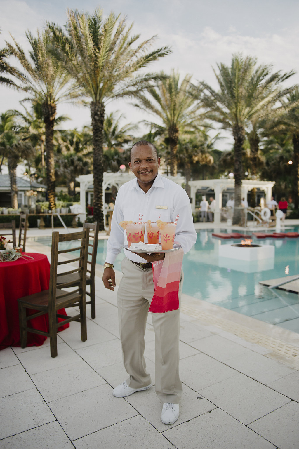 man holding a tray of beverages by a pool in late afternoon