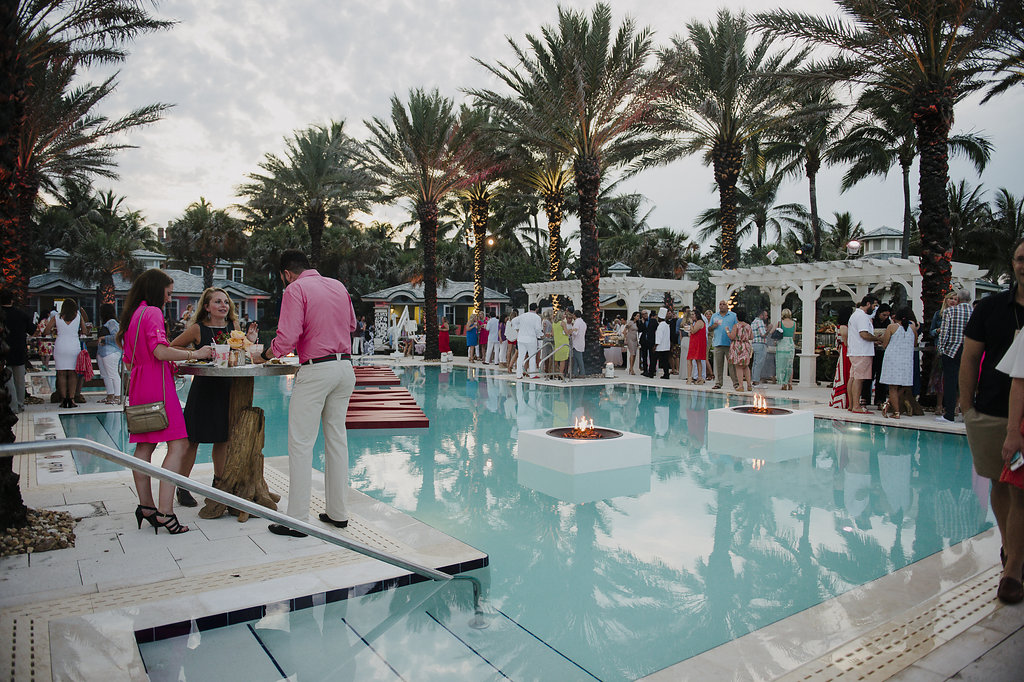 People at a party by a pool with palm trees in the background