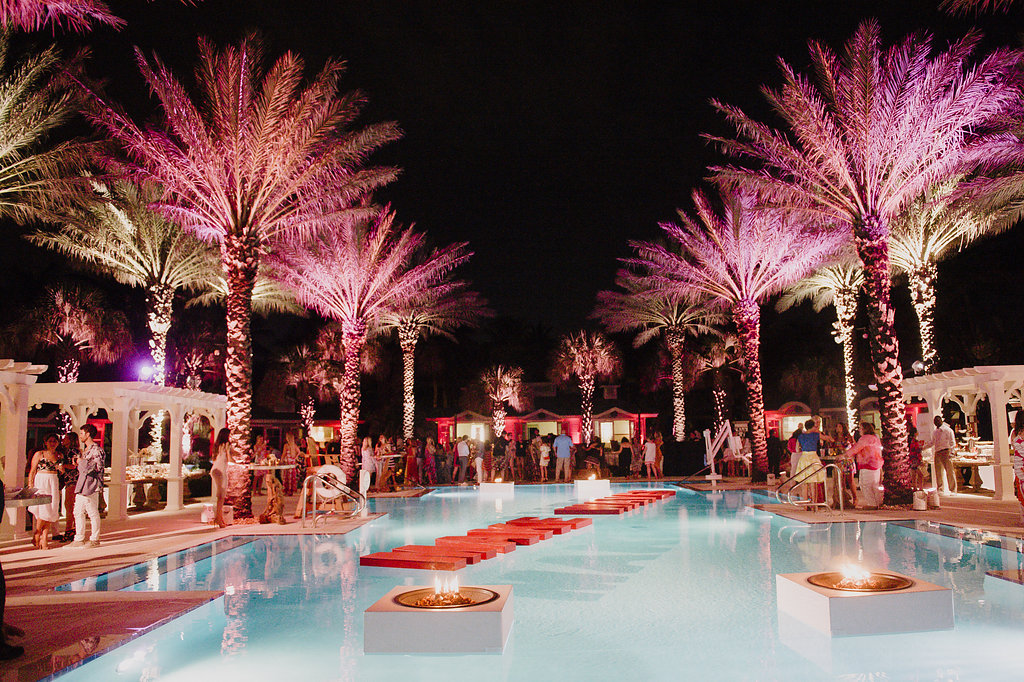 Palm trees by a pool at night with pink lights at a party