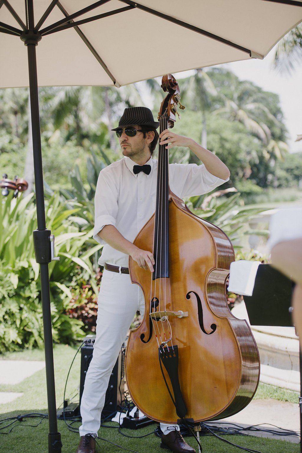Main in sunglasses and hat playing a cello outside in the shade