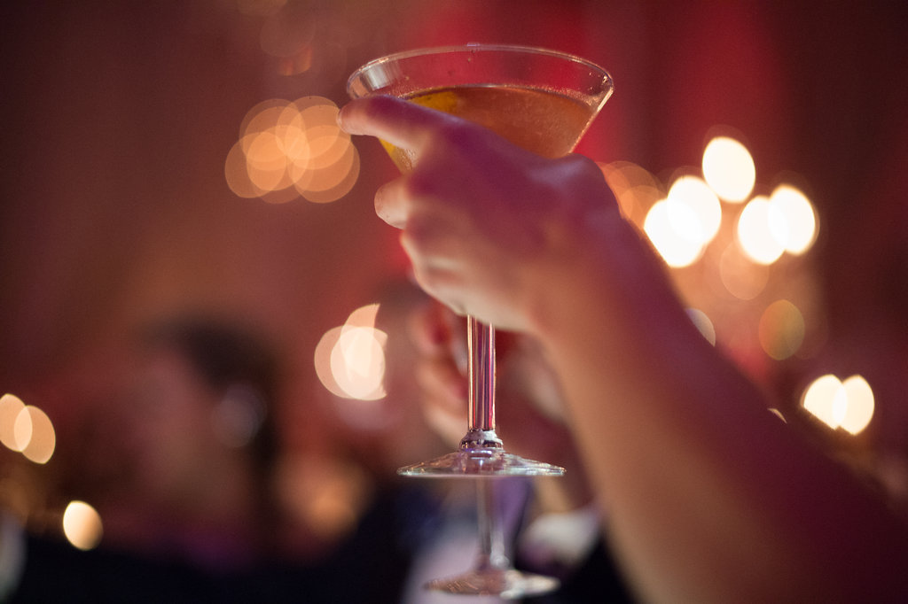 womans left hand holding a drink in a martini glass close up