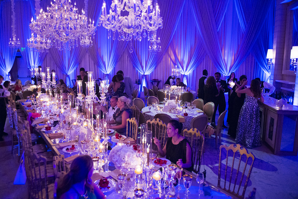 People eating and dancing in a ballroom with purple lights and chandeliers