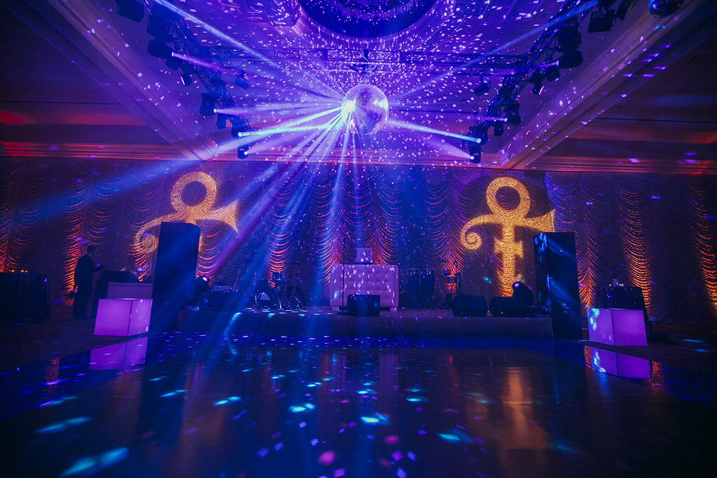 dark purple room with prince symbol on walls and disco ball