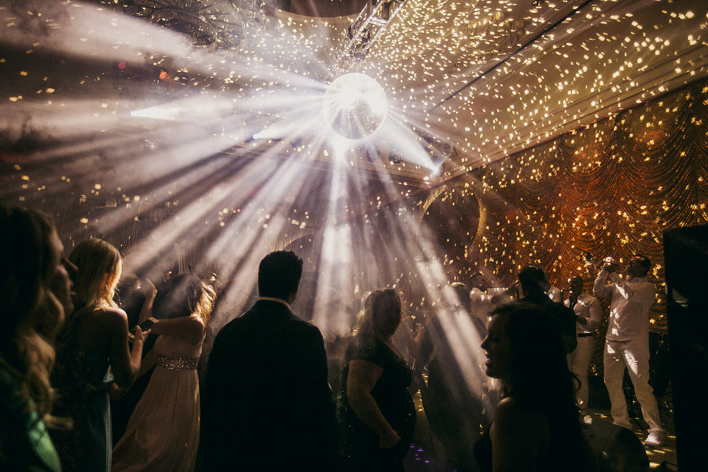 Bright disco ball streaming light in a room as people dance
