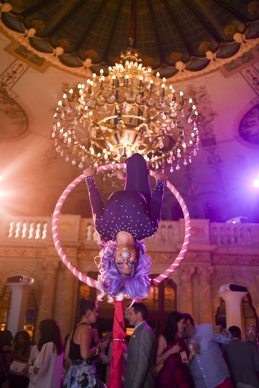 Woman suspended in a circular ring doing acrobatics