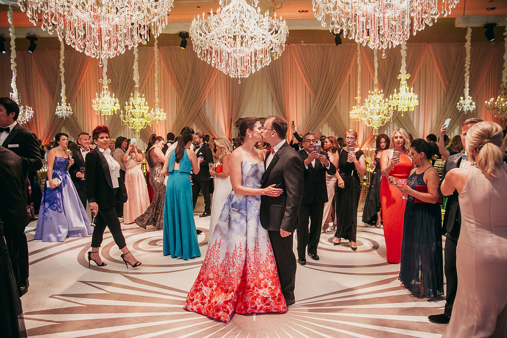 a couple kissing on a white dance floor in a room with chandeliers