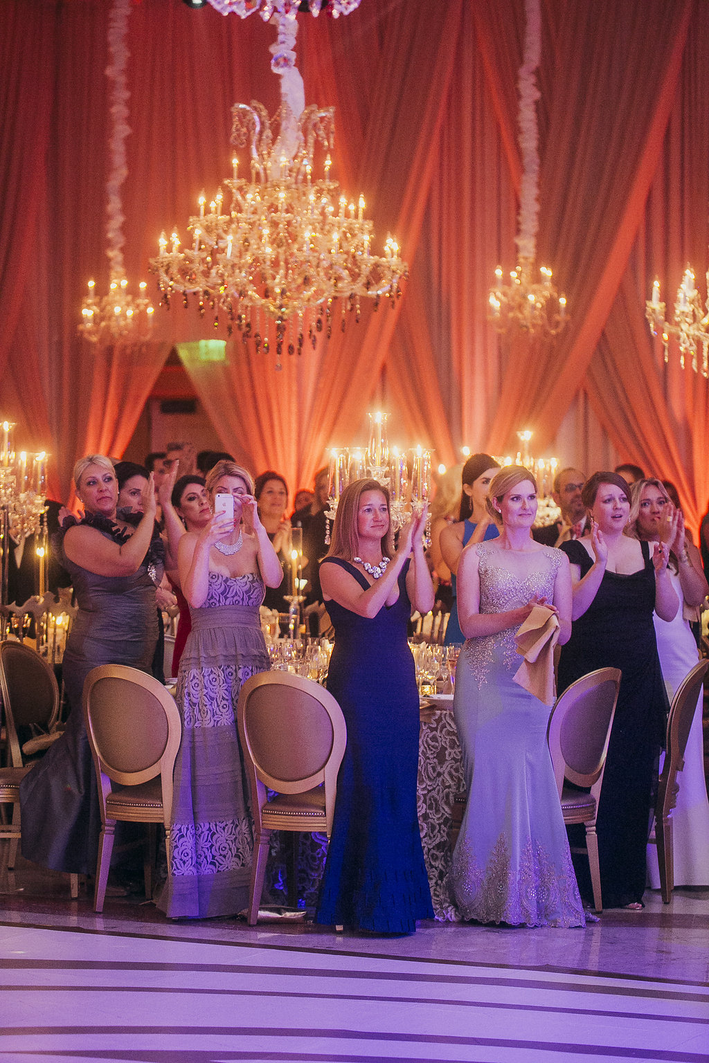 women in long gowns standing next to a dinner table in a ballroom with chandeliers