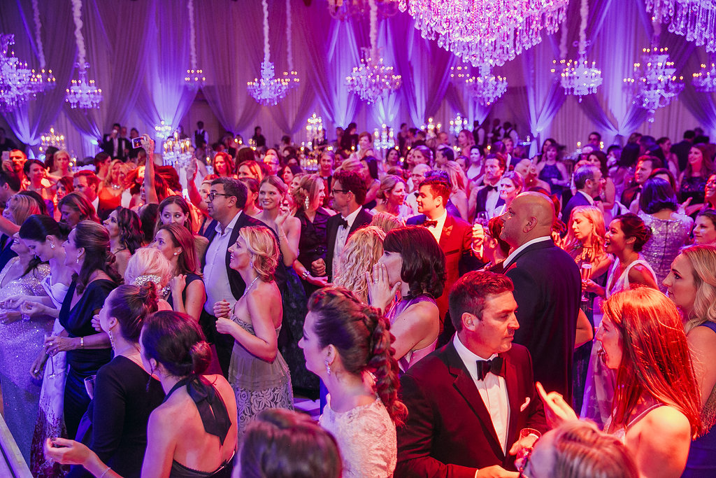 a crowd of people dressed up and dancing in a ballroom