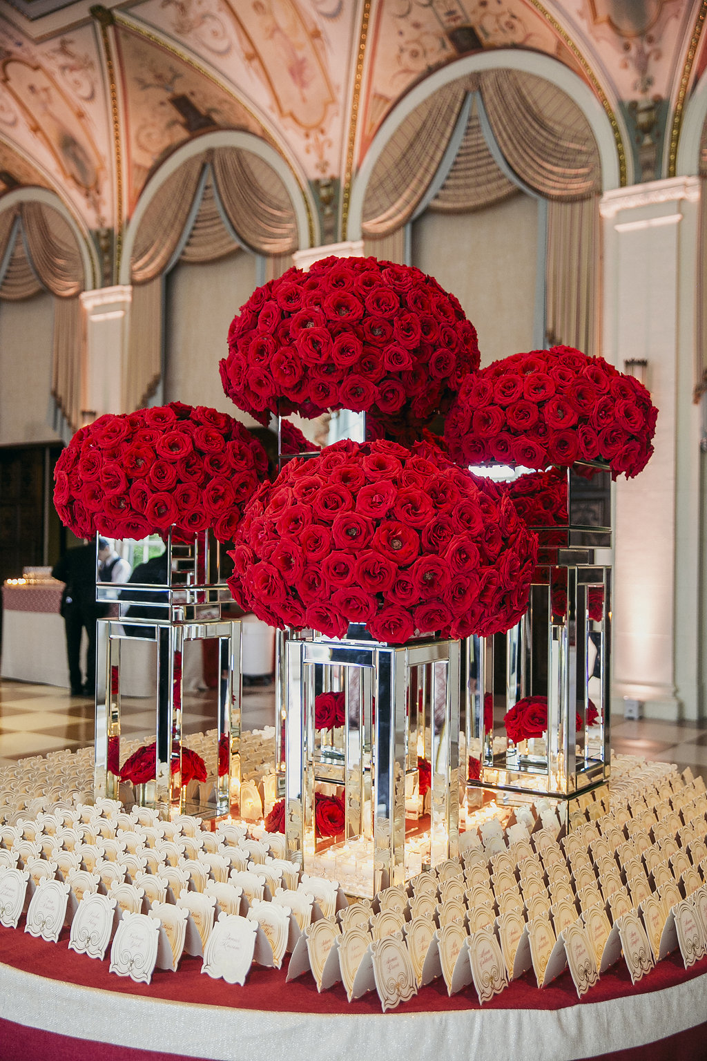 large red rose arrangements on a table with place cards in rows