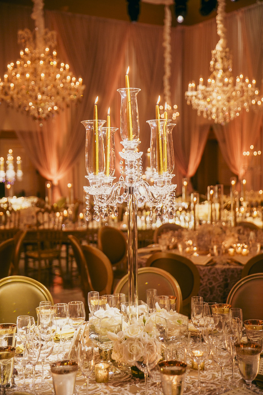 close up of candelabra on table with white flowers and candle light