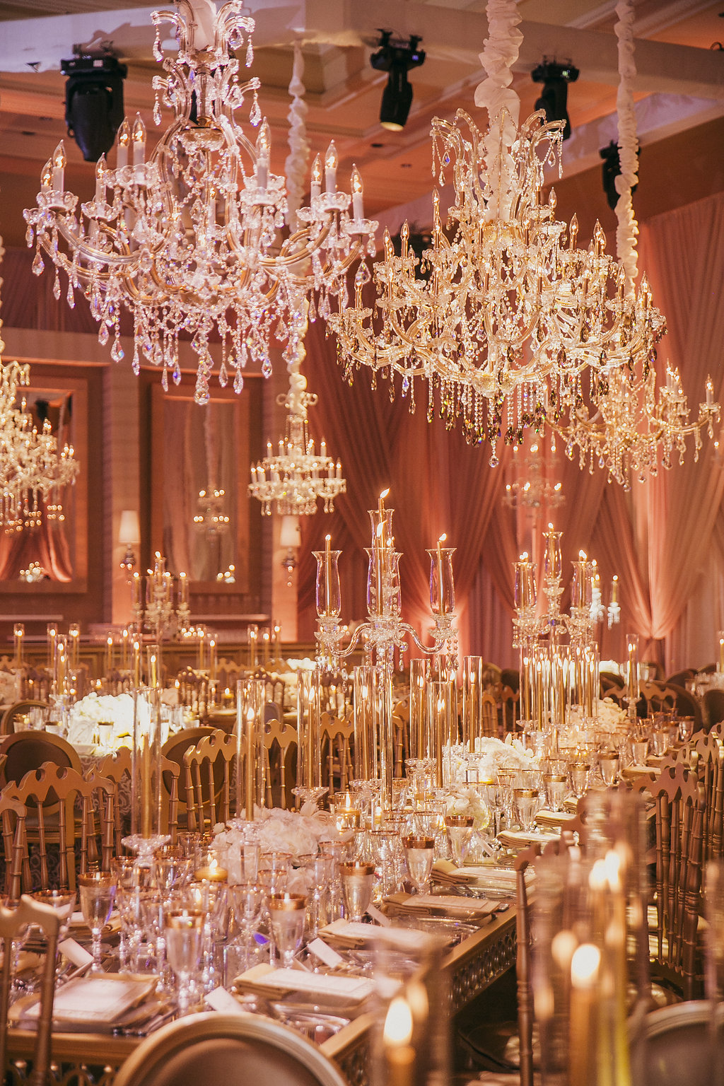 Several large chandeliers suspended over tables in a ballroom