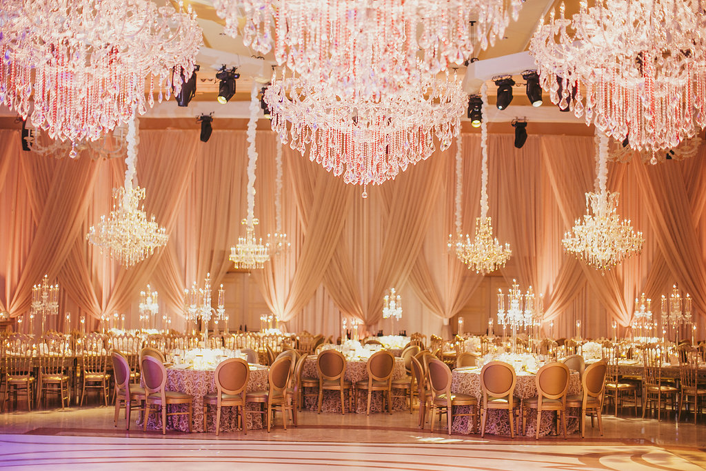Ballroom with many chandeliers over round tables with white dance floor