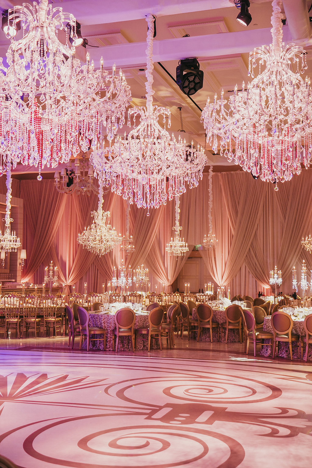photo of chandeliers over tables and white dance floor in a ballroom