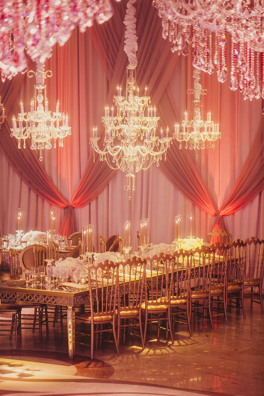 Long table set for dinner in a room wiht draped walls and chandeliers