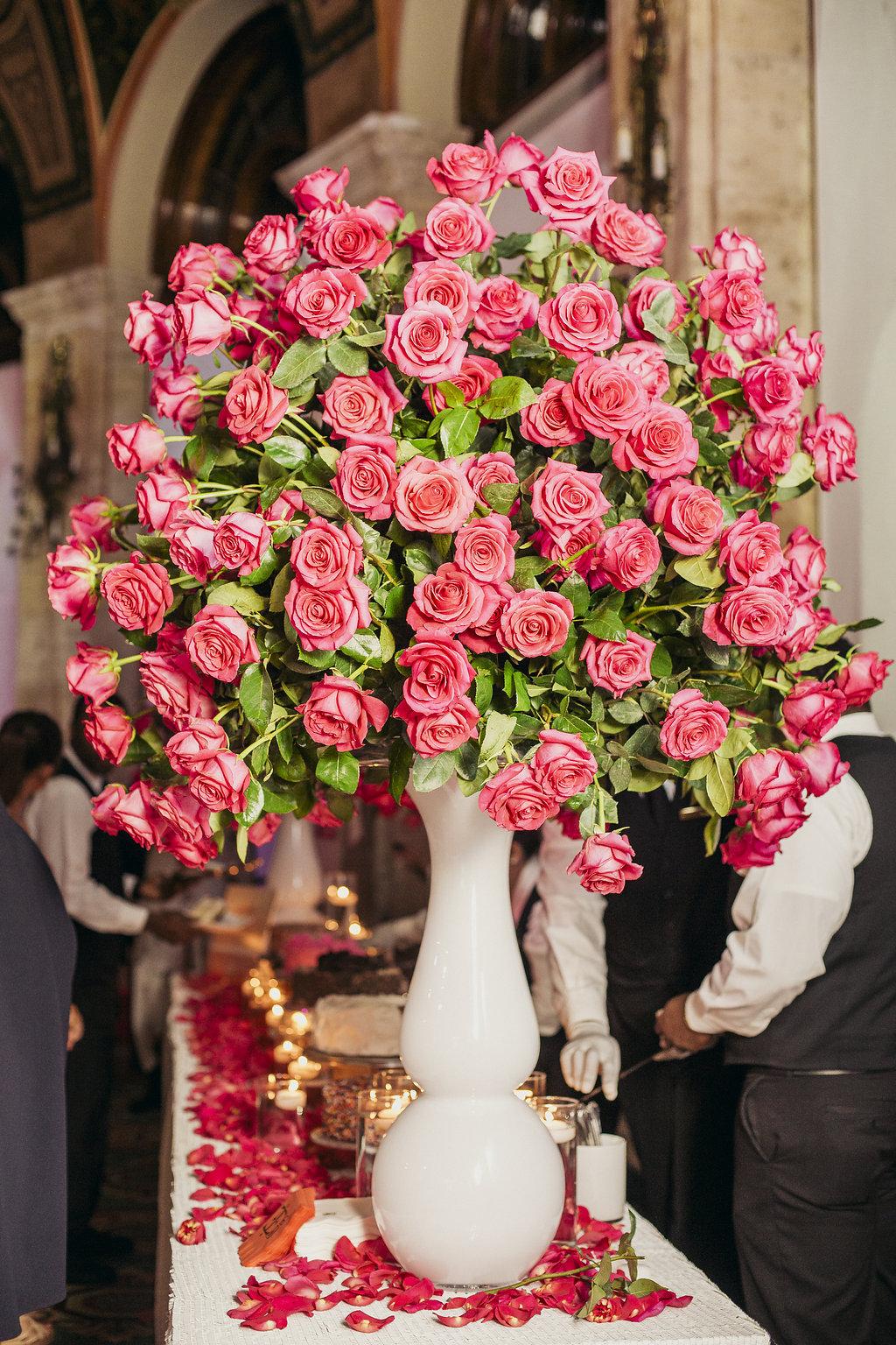 flower arrangement in a vase with many long stemmed red roses
