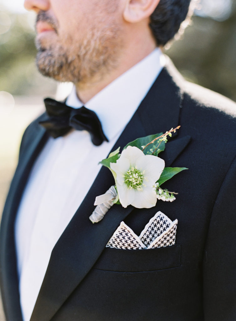 closeup of groom in a tuxedo and a white flower boutonniere on his lapel