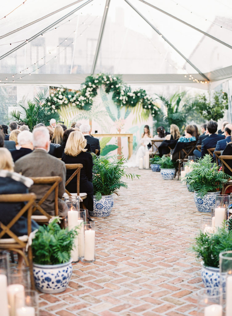 guests seating in chairs down a long aisle with potted plants and candles down the aisle