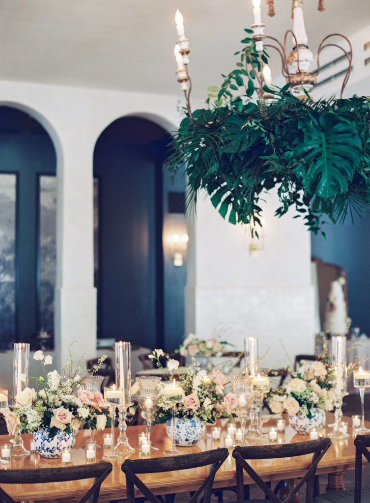 green tropical leaves hanging from a chandelier over a dinner table with pink and white flowers and clear candles at Il Mercato