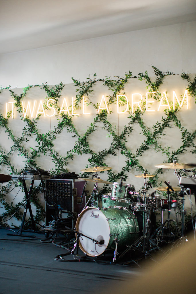 band backdrop with a drum kits and green vines in a trellis pattern and a neon sign