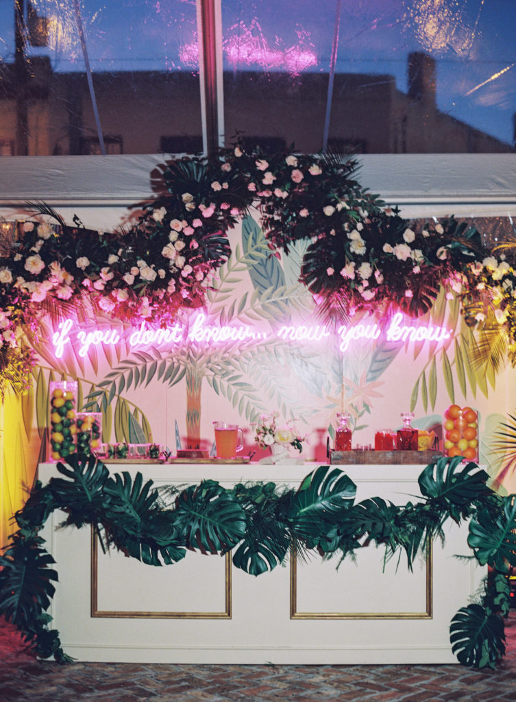 neon pink sign at a bar with tropical leaves and a tropical hand-painted backdrop