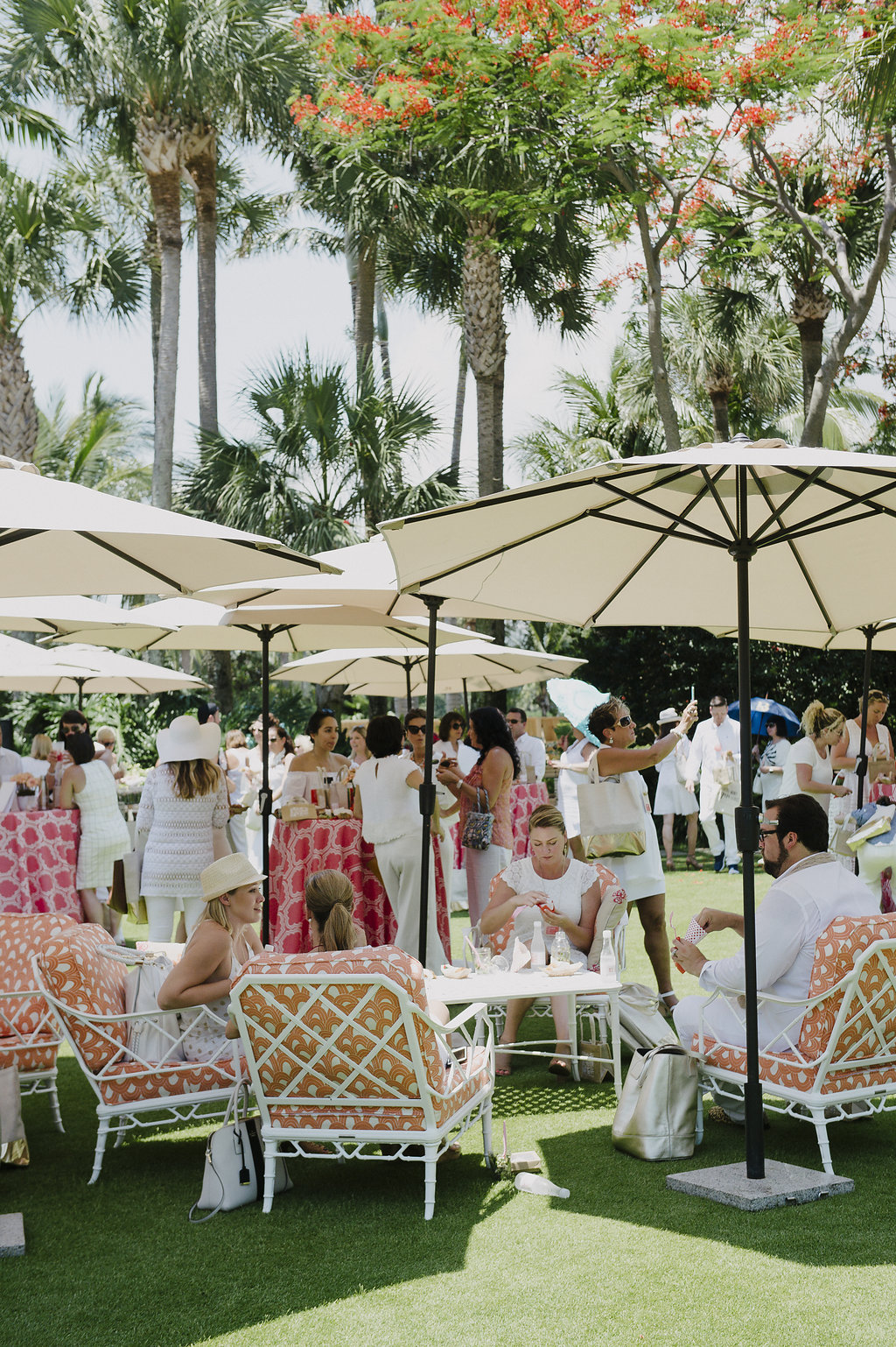 photo fo people eating picnic on a lawn dressed in white under white umbrellas