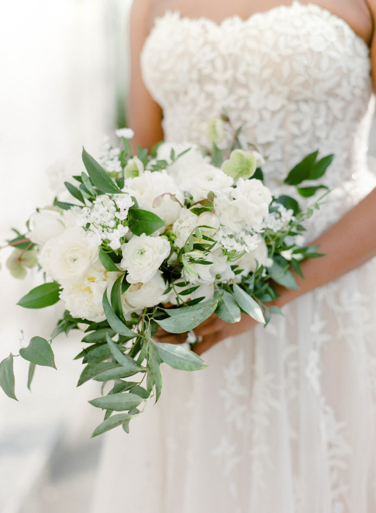 closeup of bride holding a white bouquet of flowers and green vines on her wedding day