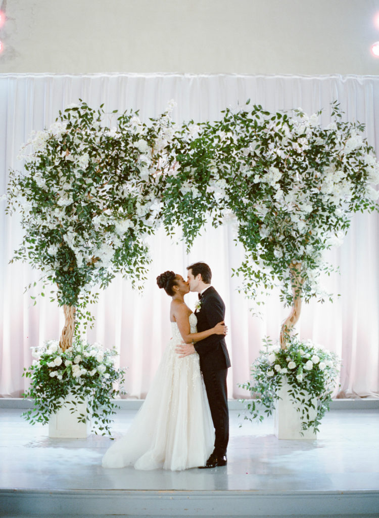 bride and groom kissing at an altar of large tree-like floral arrangements at the marigny opera house